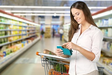 Woman with cart shopping and card wallet