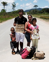 Venezuelan family from Aragua state pose for a picture as they attempt to hitchhike toward Boa Vista city, after they obtained refugee status or temporary residence, at the Pacaraima border control