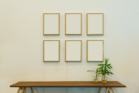 Six blank wooden picture frame on beige color wall with green plant in a glass vase on a wooden side table.