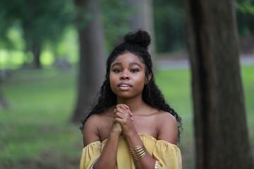Charming black woman praying outdoors