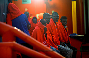 """Migrants are seen on the """"Maria Zambrano"""" rescue vessel after arriving at the port of the new Center for Temporary Assistance to Foreigners (CATE) in San Roque"""