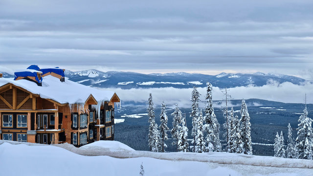 Ski Resort in winter day. Building and snow mountains covered with snow and icicles. Frosty trees. Kelowna. British Columbia. Canada.