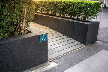 Ramped access, using wheelchair ramp with information sign on floor background