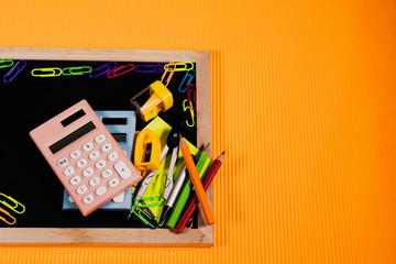 Back To School Concept. Education equipment on blackboard on orange background.
