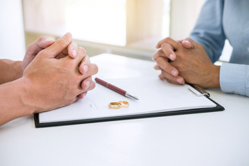 Husband and wife are reading divorce agreement and signing decree of divorce (dissolution or cancellation) of marriage filing divorce papers and two golden marry ring