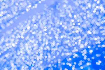 Abstract blue bokeh circles for Christmas background. Royalty high-quality free stock photo of Christmas light overlay background. Holiday glowing backdrop. Defocused background with blinking stars