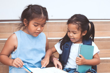 Back to school. Cute asian child girl and her sister reading a book  together with fun and happiness