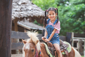 Cute asian child girl riding a pony in the farm with fun