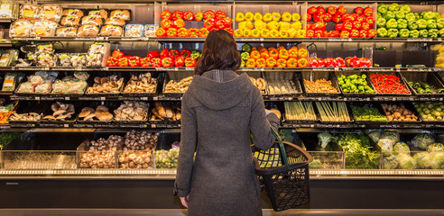 Woman standing in front of a row of produce in a grocery store. Wall mural
