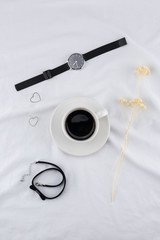A cup of coffee with woman accessories on white bed