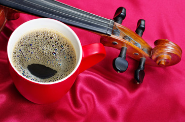 cup of coffee and a violin on a red silk background. close up.