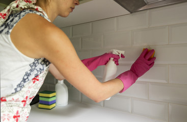 Woman cleaning kitchen tiles with spray cleaner and sponge. Household equipment, spring-cleaning, tidying up, cleaning service concept.