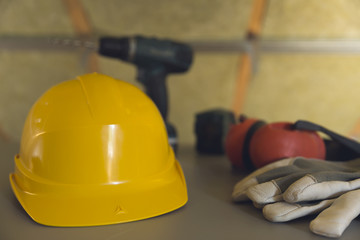 Equipment safety standard. Yellow hard hat, gloves and electric screwdriver on grey table