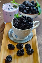 Close-up of  juicy blackberries in a bowl on rustic table and milk and berry milkshake