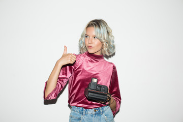 Beautiful girl in pink velvet blouse holding retro camera in hand dreamily looking aside while showing thumb up gesture over white background