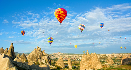 Colorful hot air balloons flying over volcanic cliffs at Cappadocia, Anatolia, Turkey. Panorama