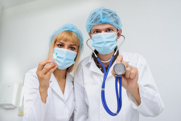 Two doctors with the masck, stethoscope in hand and injection