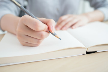 Attractive office worker writing in notepad placed on bright desktop