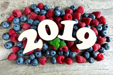 Year 2019 with blueberries and raspberries on a wooden background. Top view