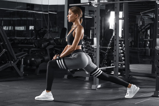 Fitness woman doing lunges exercises for leg muscle workout training in gym. Active girl doing front forward one leg step lunge exercise
