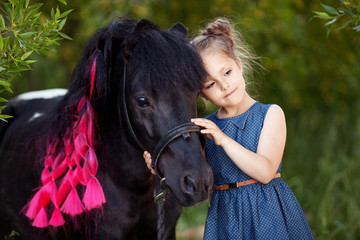 Cute little girl and pony in a beautiful park