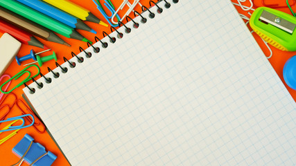 Office table with notepad, multicolored pencils, paper clips, paper binder on an orange background. View from above with copy space