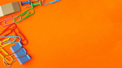 Paper clips and paper binders on orange background. View from above with copy space
