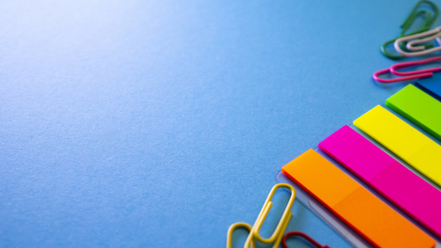 Multicolored paper clips and bookmarks on blue background. View from above with copy space