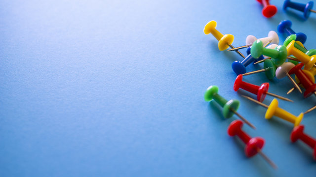 Color push pins on blue background for copyspace. Concept of office administrator business, financial inspector or secretary. View from above with copy space