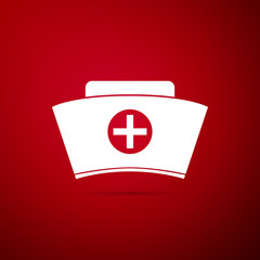 Nurse hat with cross icon isolated on red background. Medical nurse cap sign. Flat design. Vector Illustration