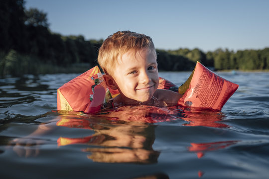 5-6 year old boy learns to swim. Active happy child wearing safe swimmies