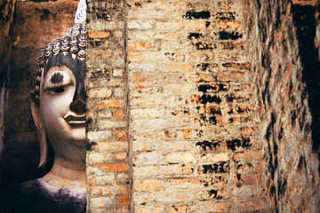 Buddha statue and the old pagoda at Wat Sri Chum temple is ancient of world heritage Sukhothai Historical Park, Sukhothai province, Thailand