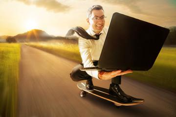 Geschäftsmann mit Laptop auf Skateboard