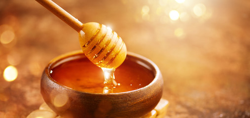 Honey. Healthy organic thick honey dripping from the honey dipper in wooden bowl. Sweet dessert background