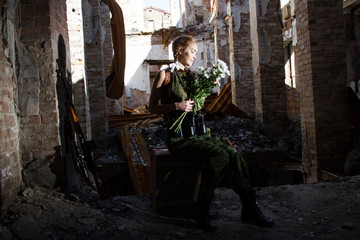 sniper girl sits in the ruins of a house with a bouquet of flowers