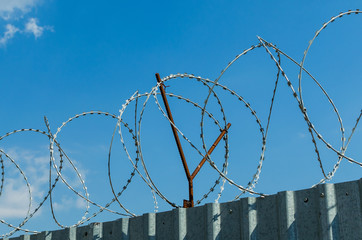 Metal fence with barbed wire on blue sky background