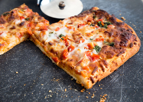 Square slices of delicious Italian style margarita pizza on board with cutter