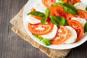 Close-up photo of caprese salad with ripe tomatoes, basil, buffalo mozzarella cheese. Italian and Mediterranean food concept. Fresh and healthy organic meal. Starter and antipasti.