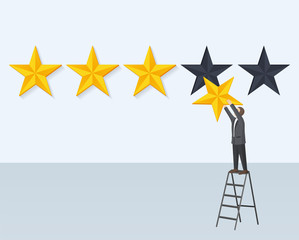 Man Hangs Rating Golden Star Stands on Step-Ladder
