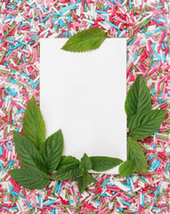 White paper with mint leaves and colorful candy sprinkles around, party design element. Festive holiday background with copy space. Celebration concept.