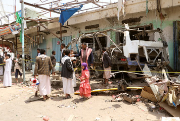 People gather next to the wreckage of a bus at the scene of Thursday's air strike in Saada province, Yemen
