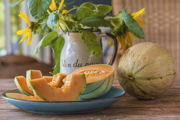 """Juicy melon slices on blue plate and bouquet of sunflowers in vintage jug with text in french """"wine of country"""" on wooden background"""