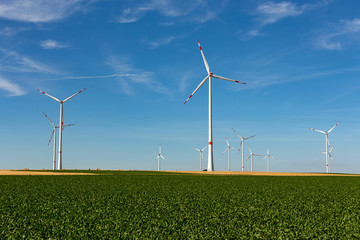 White wind turbines with red stripes generating electricity