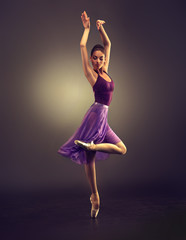 Ballerina. Young graceful woman ballet dancer, dressed in professional outfit, shoes and violet weightless skirt is demonstrating dancing skill. Beauty of classic ballet dance.