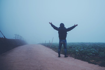 Asian man relax in the holiday. Happy to travel in the holiday. During the foggy winter