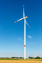 Wind turbine generating electricity on a bright blue sky.