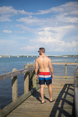 Young White Man Walking Down Florida Pier in Swim Trunks