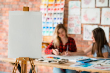 drawing lessons. art classes. painting school. learn to create pictures. blank canvas or watercolor paper on easel. empty space for advertisement. students and pictures in the background