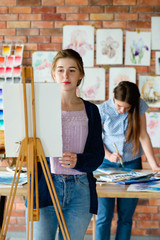 painting art classes. drawing courses. skills imagination and inspiration. student girl creating picture on easel.