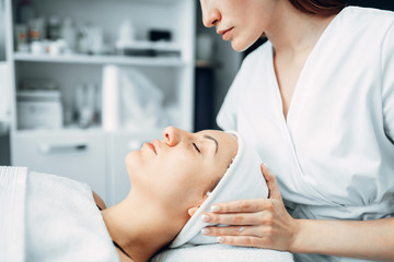Beautician makes face massage to female patient